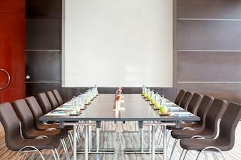 Sala de reunião vazia com mesa e quadro branco
