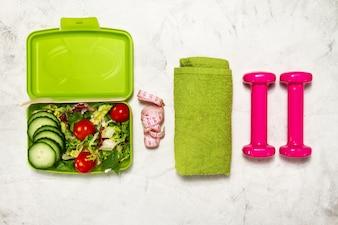 Salada com halteres e uma toalha verde