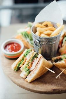 Sanduíche, batata frita e molho na tábua de madeira