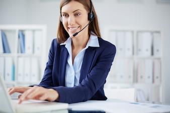 Secretária de sorriso que datilografa no portátil