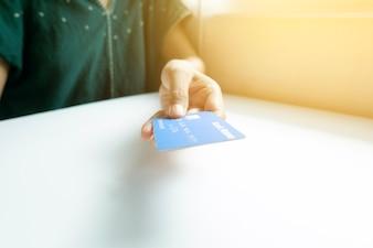 Segurando e dando cartão de crédito. Compras on-line, negócios on-line