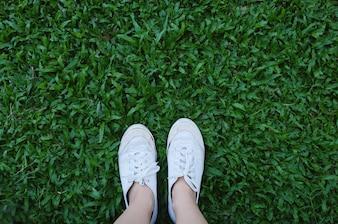 Selfie dos pés em tênis sapatos em fundo grama verde com cópia espaço, primavera e verão conceito