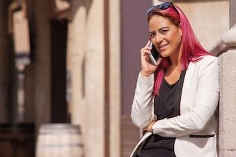 Senhora falando no celular na rua