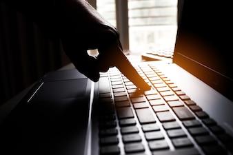 Silhouette mãos em preto e branco de hackers anônimos digitando código no teclado do laptop para alcançar e receber remotamente informações pessoais de rede online, Internet Crime Payment Security Concept