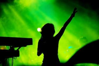 Silhueta de mulher cantando no fundo verde