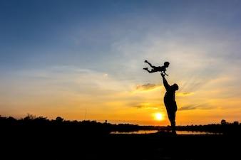 Silhueta do pai que joga o filho no céu. Pai e filho no fundo do pôr-do-sol