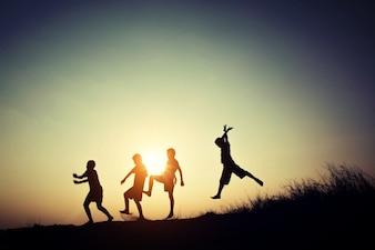 Silhuetas das crianças que jogam no por do sol