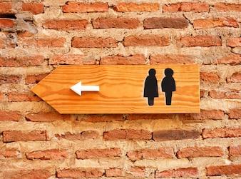 Sinal e direção do banheiro na parede de tijolos