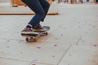 Skate de equitação adolescente na bandeira de pavimentação