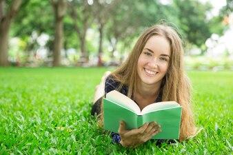 Smiling Beautiful Girl Deitada na grama com o livro
