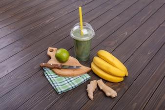 Smoothie saudável com bananas, limão e gengibre deitam-se sobre a mesa
