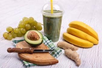 Smoothie verde com bananas, limão, uva e abacate encontram-se na mesa