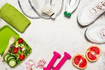 Sneakers, uma salada, raquetes de badminton e frutas