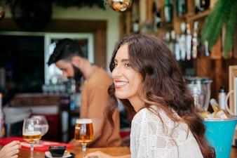 Sorridente jovem com cerveja no bar