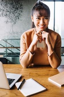 Sorridente mulher segurando o telefone