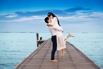 Sorrindo abraço de jovem casal enquanto está de pé na ponte de madeira; madeira