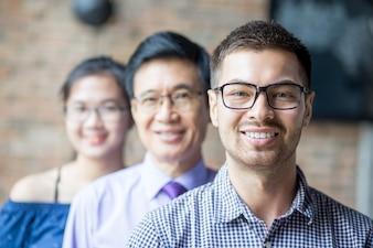 Sorrindo equipe de negócios diversa em pé na fila