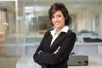 Sorrindo executivo com terno preto e os braços cruzados