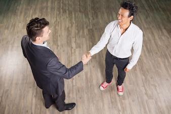 Sorrindo homens de negócios Reunião e que agita as mãos