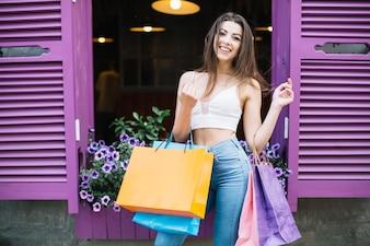 Sorrindo menina com pacotes na rua