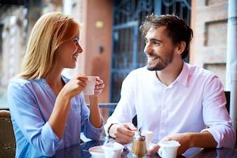 Sorriso do café casal bebendo e olhando para o outro