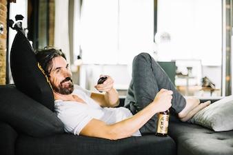 Sorriso homem com cerveja desfrutando TV