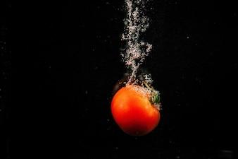 Sparkling tomate vermelho cai na água e espirra-lo