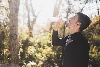 Sportsman beber água em um dia ensolarado