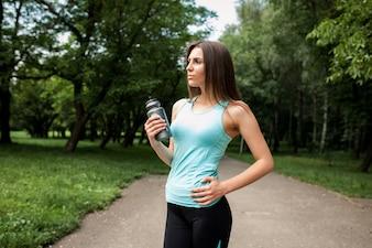 Sportswoman em um parque com uma garrafa de água na mão