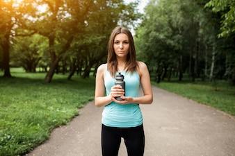 Sportswoman em um parque com uma garrafa de água nas mãos