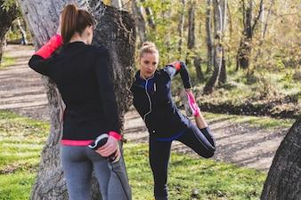 Sportswomen estica os pés ao ar livre