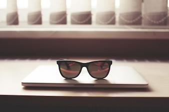 Óculos de sol no laptop fechado