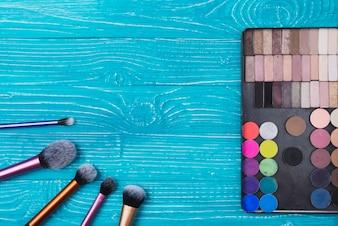 Superfície azul com pós e make-up escovas