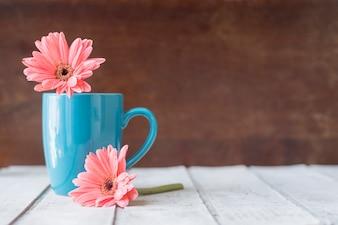Superfície de madeira com caneca azul e flores decorativas