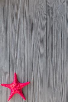 Superfície de madeira com estrela do mar roxa