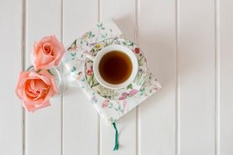 Superfície de madeira com livros, flores e copo do chá