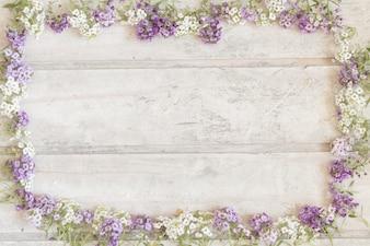Superfície de madeira com quadro feito de flores roxas e brancas