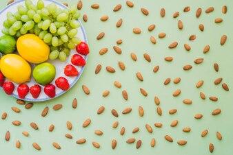 Superfície verde com várias frutas saborosas e amêndoas