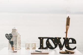 Tabela branca com lanternas decorativas e letras de aço AMOR