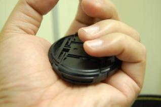 tampa da lente na mão