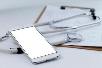 Telefone celular, estetoscópio e arquivo gráfico na área de trabalho (médicos móveis, conceitos de médicos portáteis)