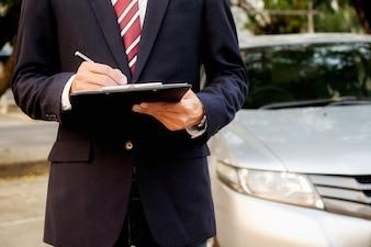 Tempo para tomar uma decisão. Jovem empresário confiante trabalhando em seu lablet e falando ao telefone enquanto está sentado no carro