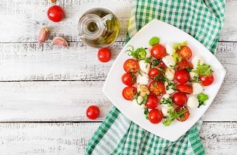 Tomate salado Caprese e mussarela com manjericão e ervas em um prato branco