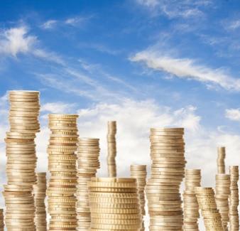 Torres altas de moedas que representam a riqueza sob um céu azul