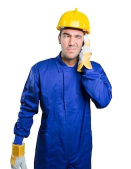 Trabalhador preocupado cobrindo os ouvidos com as mãos no fundo branco