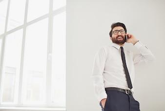 Trabalhador que fala no telefone perto da janela