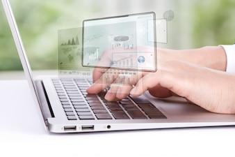Trabalhador que olha um portátil gráficos