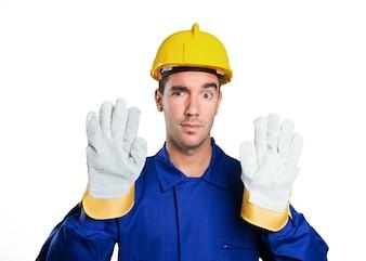 Trabalhador sério com gesto de parada no fundo branco