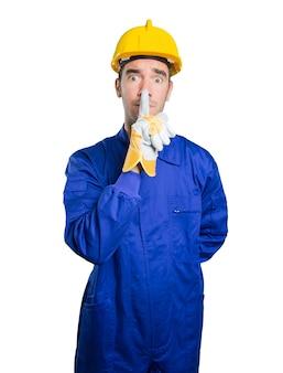 Trabalhador sério com gesto de silêncio no fundo branco