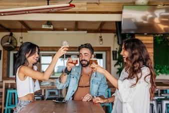 Três amigos brindando com cerveja